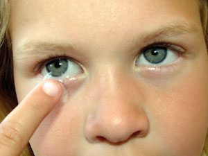 Child inserting contact lenses