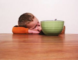 boy asleep at table with breakfast bowl