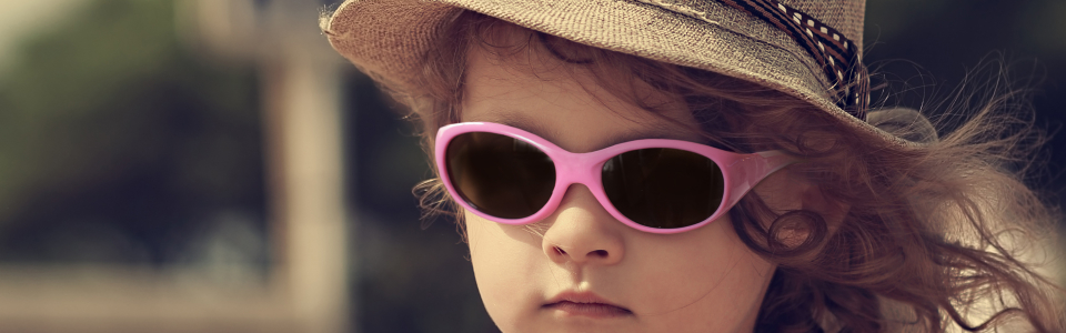 Kid in sun glasses and fashion hat outdoors. Vintage