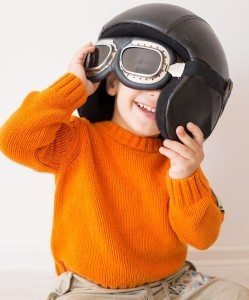 Little cute playful baby kid with pilot hat and goggles ready fo